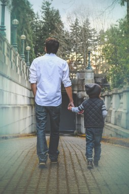 Photo of father walking and holding son's hand.