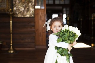 Photo of young girl holding a bouquet of roses.