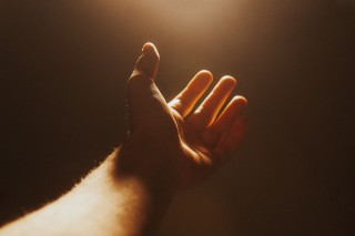photo of outstretched hand toward light
