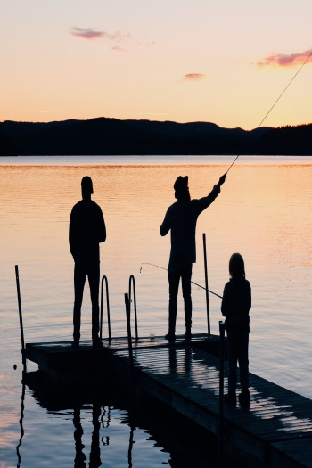 Photo of Three People on a Wooden Dock Fishing by Olof Nyman from Pexels