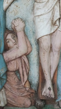 Mary Magdalen kneeling at the foot of the cross.
