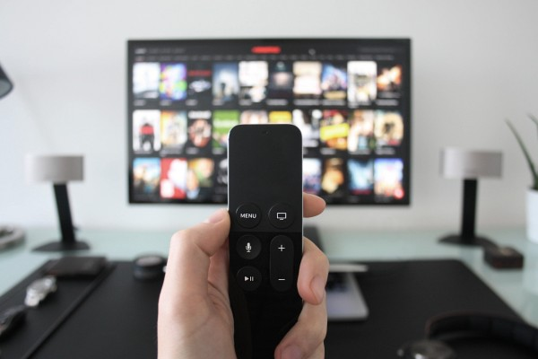 Photo of hand holding tv remote with tv in background
