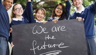 Photo of school kids holding sign that reads We are the Future